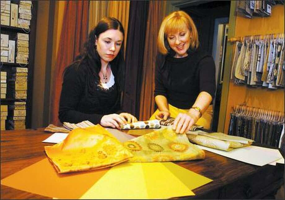 Repaint your walls when you get bored or tired of them, says Kathy Banak, right, the owner of Authentic Home stores. With her is associate designer Niky Bryant. Photo: Steve Shelton/Special To The Seattle Post-Intelligencer