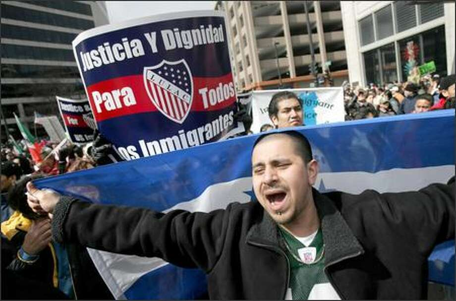 "Jose Molina, carrying a Honduran flag, marches in the ""Day Without Latinos"" rally for immigration rights Thursday in Milwaukee. Photo: / Associated Press"