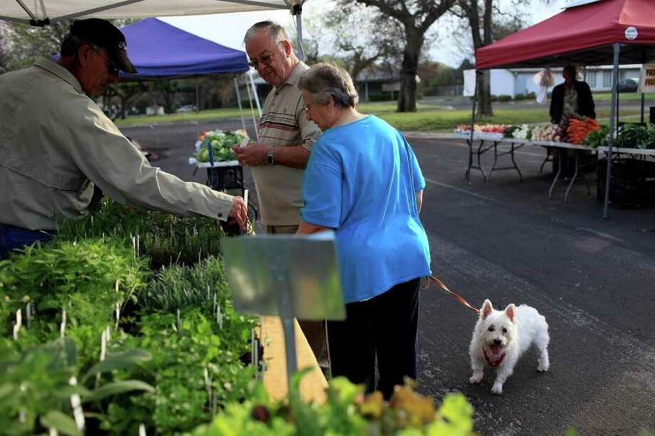 Michael and Gabriele McNiff, with their dog, Jenny, shop for herbs from Juan Gonzalez (left) at the Auntie Pen's Backyard Herbs booth at the Farmer's Market in Leon Valley. Photo: Lisa Krantz/Express-News / SAN ANTONIO EXPRESS-NEWS