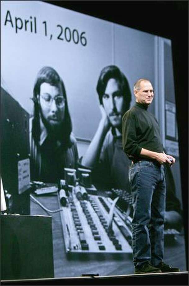 Steve Jobs, right, smiles at a 30-year-old photo of himself, right, and Apple co-founder Steve Wozniak. Photo: / Associated Press