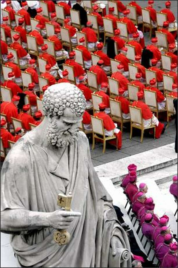 A statue of St. Peter dominates the view as cardinals and bishops attend the elevation Friday by Pope Benedict of 15 new cardinals. Photo: / Associated Press