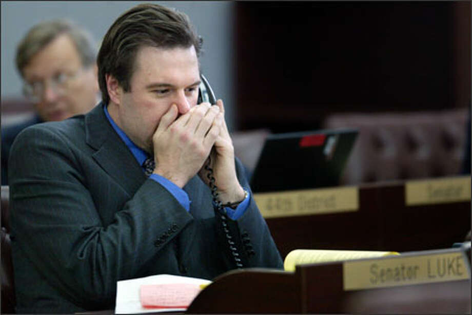 The seat of state Sen. Luke Esser, R-Bellevue, seen quietly speaking on a phone during a legislative session, is being targeted by Washington Democrats. Photo: Karen Ducey/Seattle Post-Intelligencer
