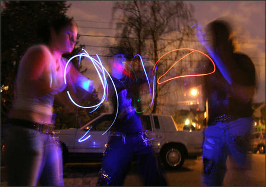 "Near the scene of the Capitol Hill shootings, Giggles, 16, left, and Nemesis, 19, center, do a light show on the street as a tribute to ""Sushi,"" their friend who was killed on Saturday. Photo: Meryl Schenker/Seattle Post-Intelligencer"