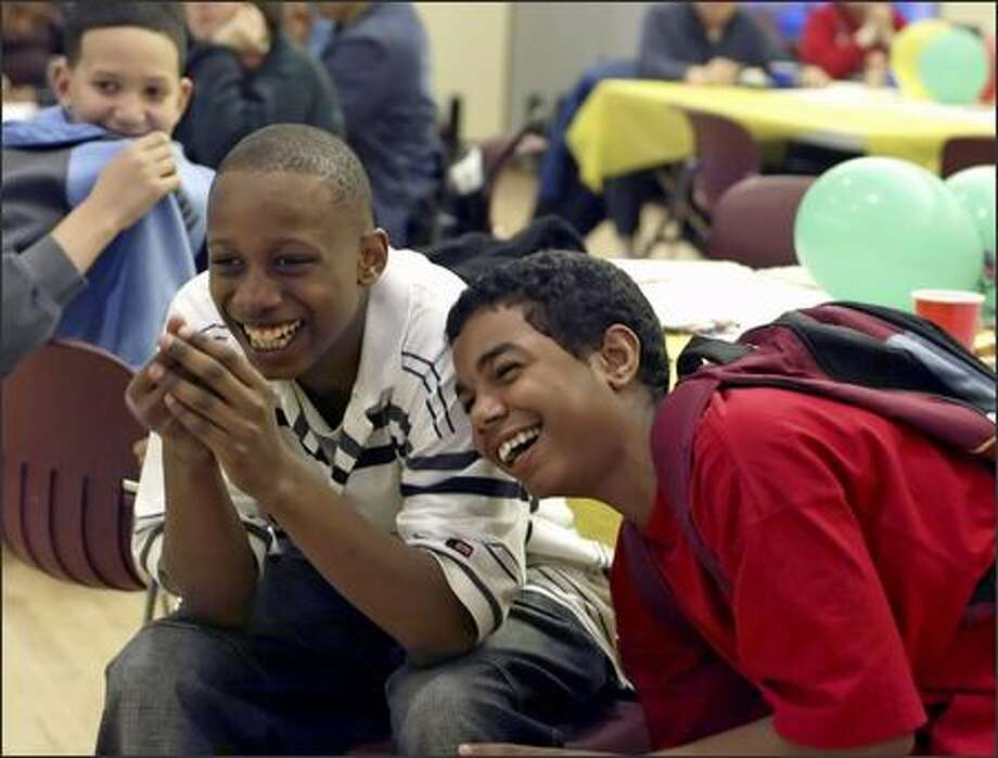 Dnique Harris-Welch, left, Jerome Jackson and Darvell Maud enjoy a video from children in Louisiana on Friday at Delridge Community Center in Seattle. Photo: Jim Bryant/Seattle Post-Intelligencer