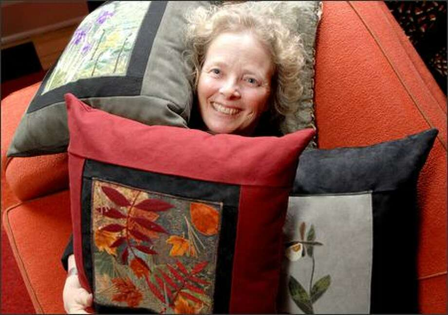 "Susan Holland is surrounded by her hand-stitched pillows, most of which will be available at Best of the Northwest. ""I am drawn to nature and botanical themes,"" she says. Photo: Steve Shelton/Special To The Seattle Post-Intelligencer"
