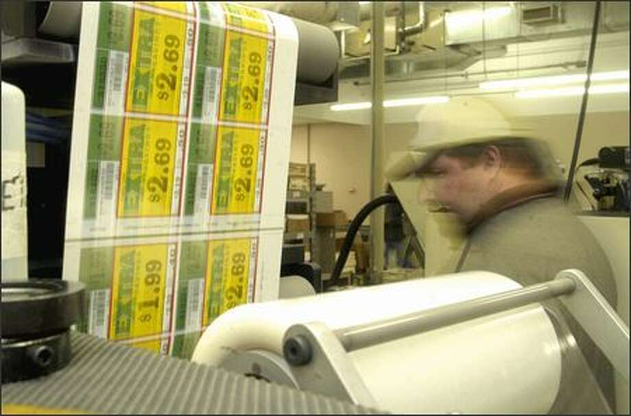 Bobby Morris, an employee at Vestcom, makes shelf tags, which are used in thousands of stores. Photo: / Associated Press