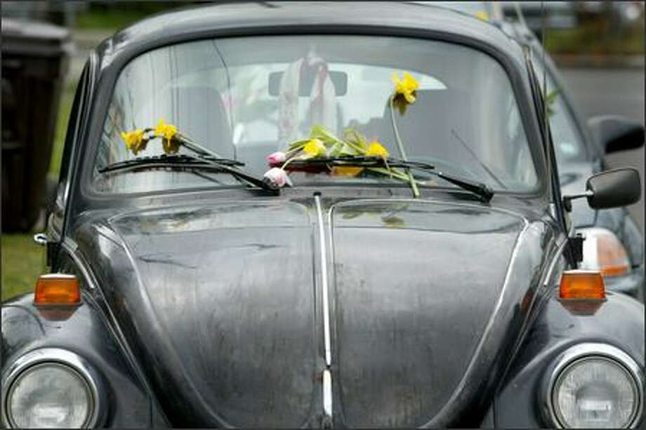 Flowers adorn a car parked Wednesday at the house where seven people were killed Saturday. A mourner at the scene said it belonged to a victim. Photo: Joshua Trujillo/Seattle Post-Intelligencer