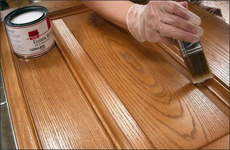 A coat of urethane is applied to a fiberglass door Photo: /