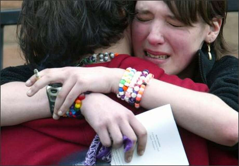 "Mary Miller, 15, of Seattle hugs a friend Thursday outside Lake City Presbyterian Church at a memorial service for Chris Williamson. ""We are burying one of our friends,"" Miller said. ""It just can't be true."" Photo: Karen Ducey/Seattle Post-Intelligencer"