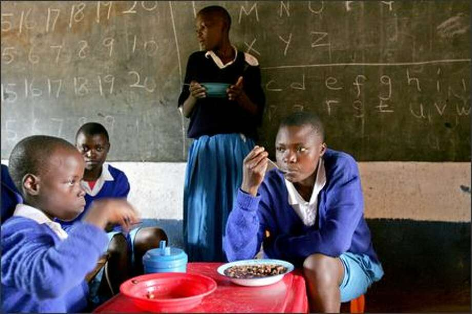 Schoolchildren eat lunch provided by the Millennium Village Project in Sauri, Kenya. The program will be expanded to 55,000 villages. Photo: / Associated Press