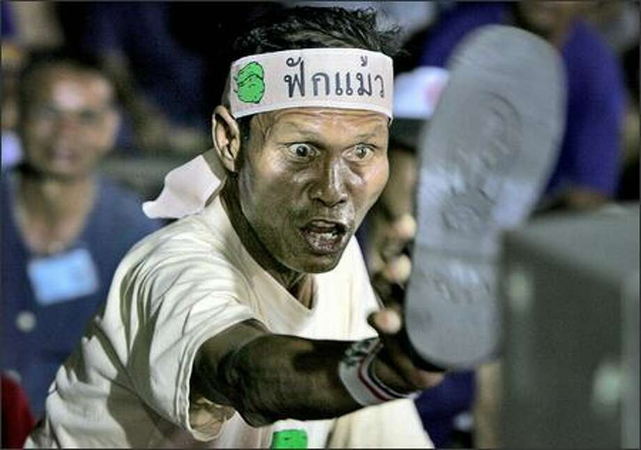 Thai protester Kao Chantaman insults an address by Thai Prime Minister Thaksin Shinawatra by showing the TV screen the sole of his shoe Monday in Bangkok. Photo: / Associated Press