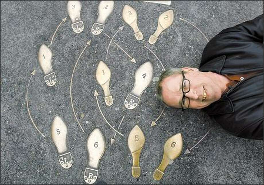 Jack Mackie, shown recently with his creation, is the artist behind the bronze dance steps on Broadway in the Capitol Hill neighborhood. Photo: Dan DeLong/Seattle Post-Intelligencer