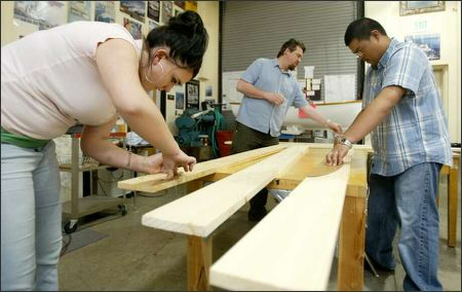 Taliesyn Steel, left, and Alvin Garcia work on wood models of a ship's hull in a class at Ballard High School's Maritime Academy taught by John Foster, center. Photo: Paul Joseph Brown/Seattle Post-Intelligencer
