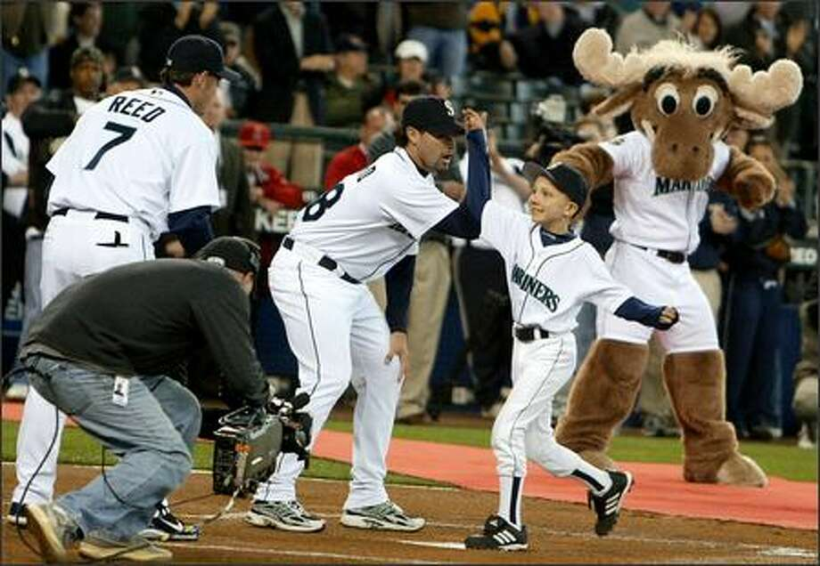 Jeffery Baker is greeted at home plate by, from left, Jeremy Reed, Joel Pineiro and the Mariner Moose. Photo: Scott Eklund/Seattle Post-Intelligencer