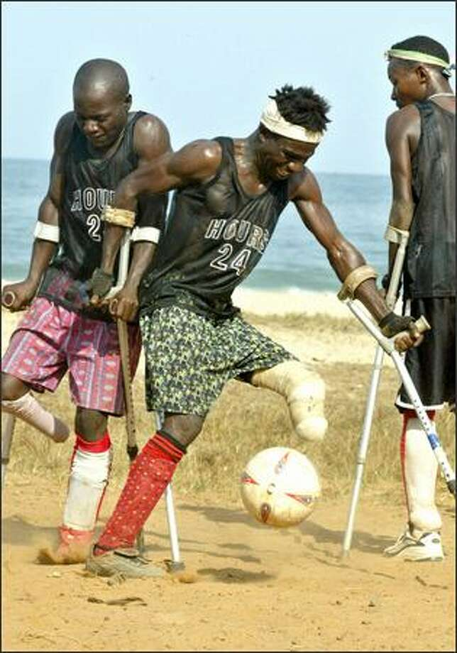 Wartime amputee Musa Vandi, center, plays soccer with amputee friends on a beach in Freetown, Sierra Leone, last Saturday. Photo: / Associated Press