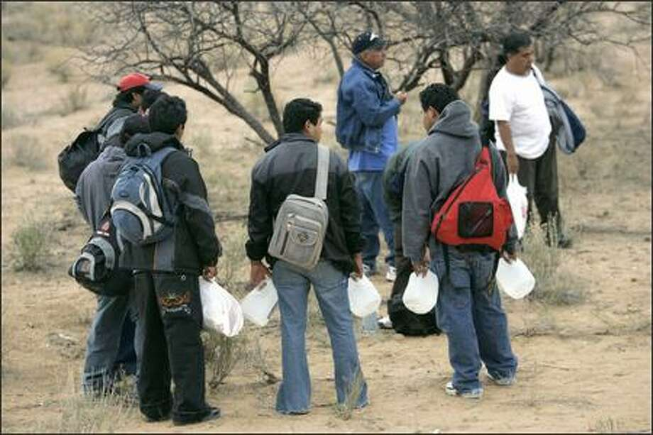 Carrying gallons of water, Mexicans wait for darkness near Sasabe, Mexico, before trying to enter the United States Tuesday. Photo: / Associated Press