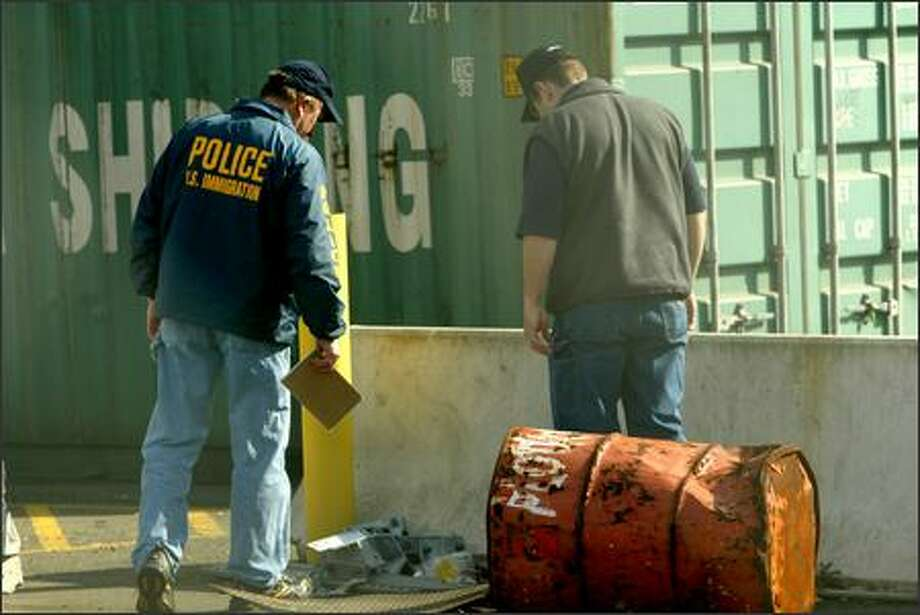 Investigators look for clues Wednesday near the cargo container that carried 22 stowaways from China to Seattle on the MV Rotterdam. Photo: Grant M. Haller/Seattle Post-Intelligencer