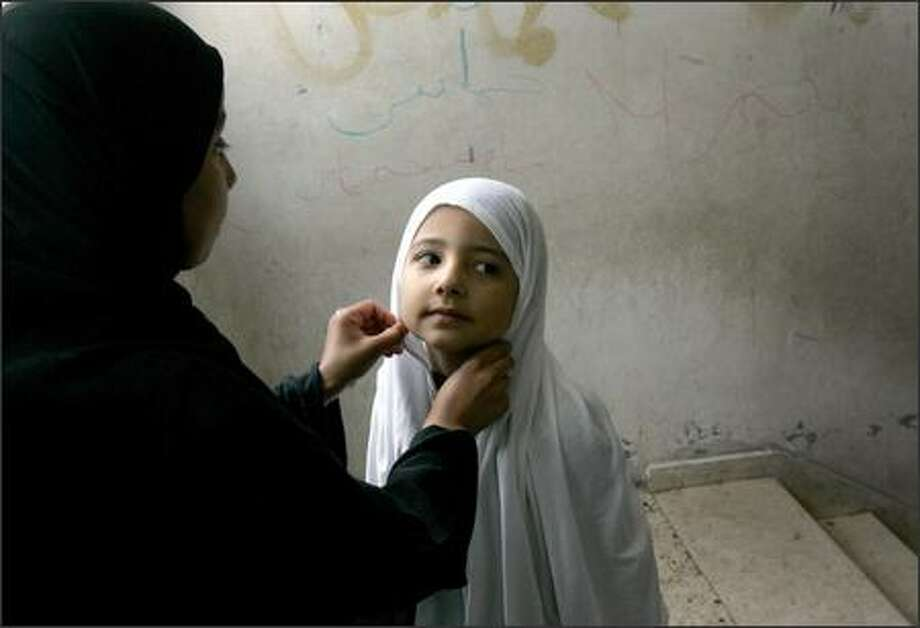 A Palestinian child has her hijab adjusted before Friday prayers at a Hamas mosque in Gaza City. The European Union has cut off direct aid payments to the Hamas-led Palestinian government. Photo: / Associated Press