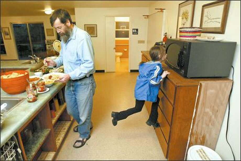 Craig Ragland, left, creates a burrito while Lily Krasle waits at the microwave for a quesadilla during a communal dinner at Songaia Cohousing Community in Bothell. Photo: Mike Urban/Seattle Post-Intelligencer