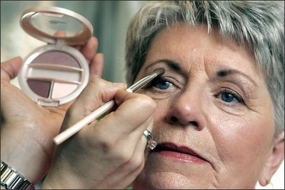 Kathleen Maguire, 66, of Mount Laurel, N.J., has Vital Radiance eye shadow applied at Revlon headquarters in New York. Vital Radiance is designed for women over 50. Photo: / Associated Press