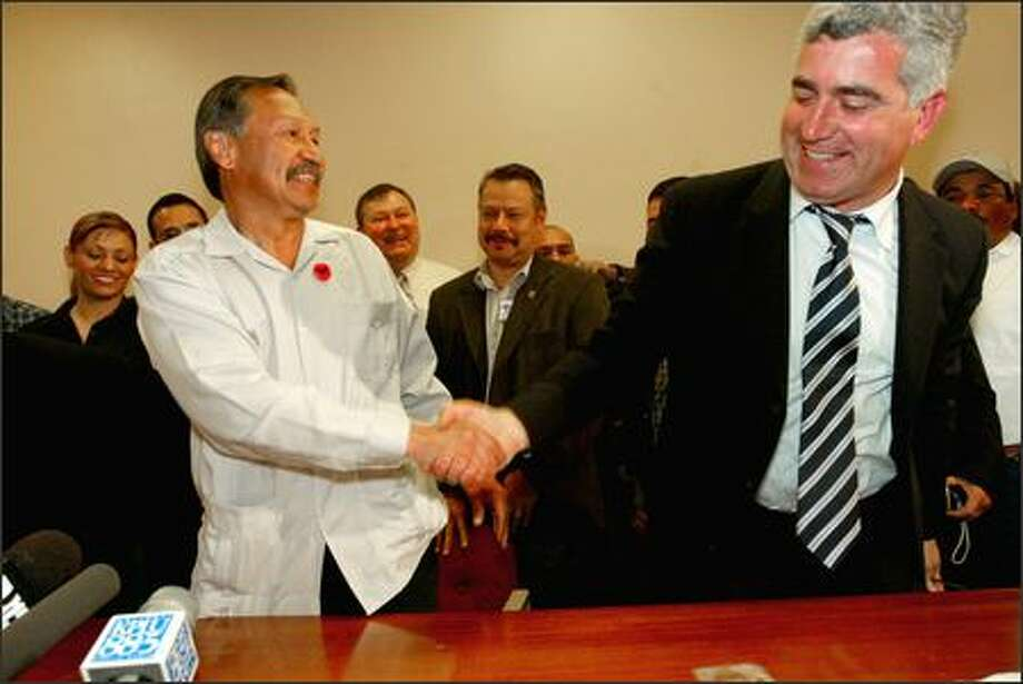 United Farm Workers President Arturo Rodriguez, left, shakes hands with Global Horizons chief Mordechai Orian after signing a pact at the Seattle Labor Temple. Photo: Grant M. Haller/Seattle Post-Intelligencer