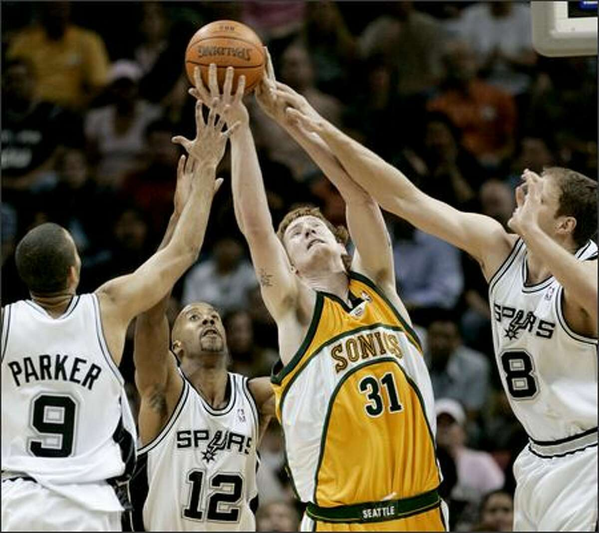 Sonics center Robert Swift reaches above three Spurs for a rebound in San Antonio's 104-95 win Tuesday night.