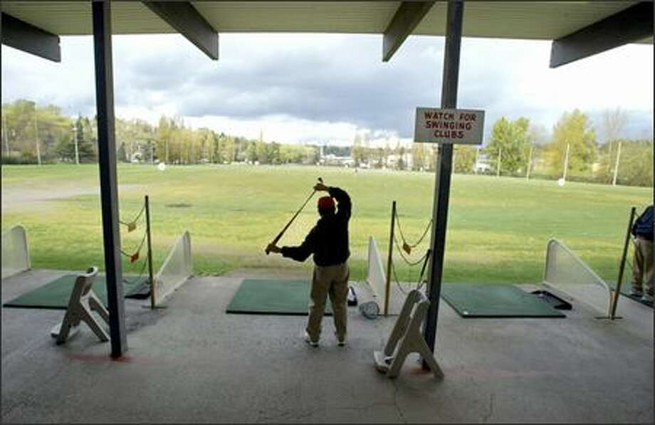 Tony Casaba of Seattle stretches before hitting a bucket of balls at the UW driving range. Students decided to no longer fund a $10 million face-lift. Photo: Meryl Schenker/Seattle Post-Intelligencer