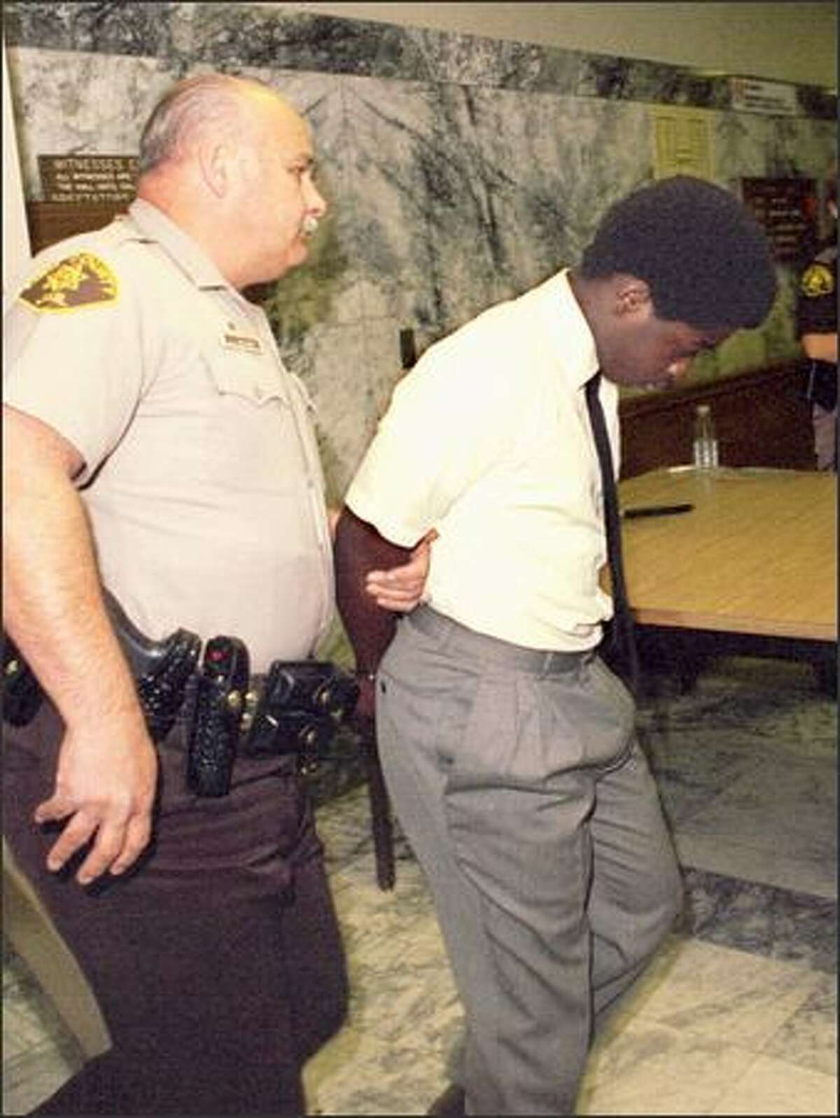 Willard Jimerson being escorted out of the King County Courthouse as a 13-year-old murder defendant.