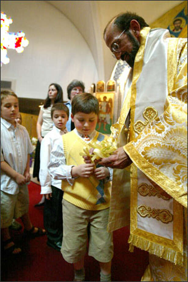 Metropolitan Gerasimos Michaleas gives a palm frond to a boy on Palm Sunday at St. Demetrios. Photo: Grant M. Haller/Seattle Post-Intelligencer