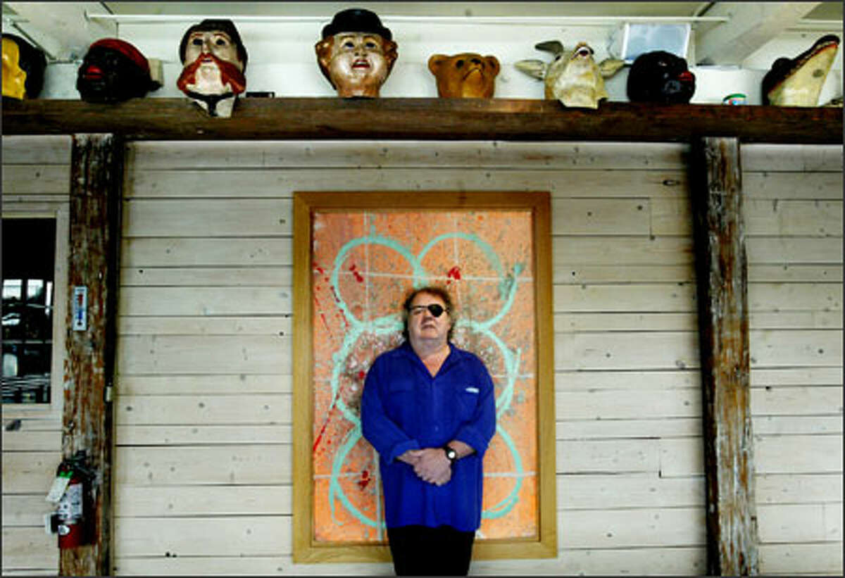 Dale Chihuly stands in front of one of his paintings in his north Lake Union building. Above are circus masks from his personal collection.