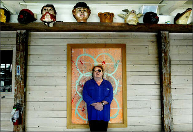 "Dale Chihuly stands in front of one of his paintings in his north Lake Union building. Above are circus masks from his personal collection. ""Nobody works harder than Dale,"" says artist Benjamin Moore. ""He never makes time for anything but his mania for glass."" Photo: Dan DeLong/Seattle Post-Intelligencer"