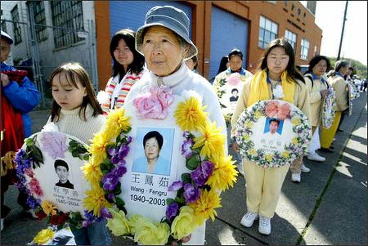 Li Li Hu holds a picture of a friend, Wang Fengru, who was allegedly killed in a concentration camp. Hu came up from Los Angeles to join Monday's march in Seattle by Falun Gong practitioners.
