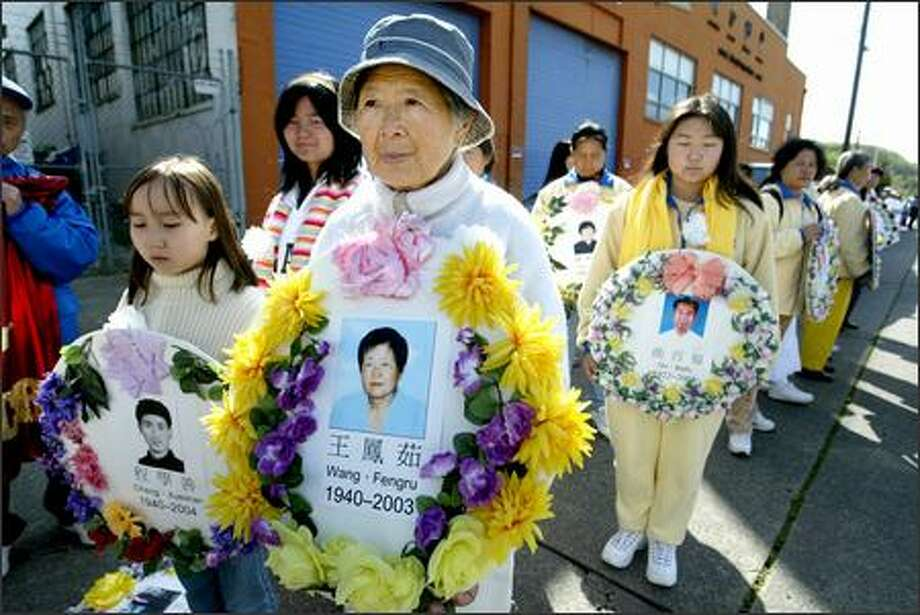 Li Li Hu holds a picture of a friend, Wang Fengru, who was allegedly killed in a concentration camp. Hu came up from Los Angeles to join Monday's march in Seattle by Falun Gong practitioners. Photo: Scott Eklund/Seattle Post-Intelligencer