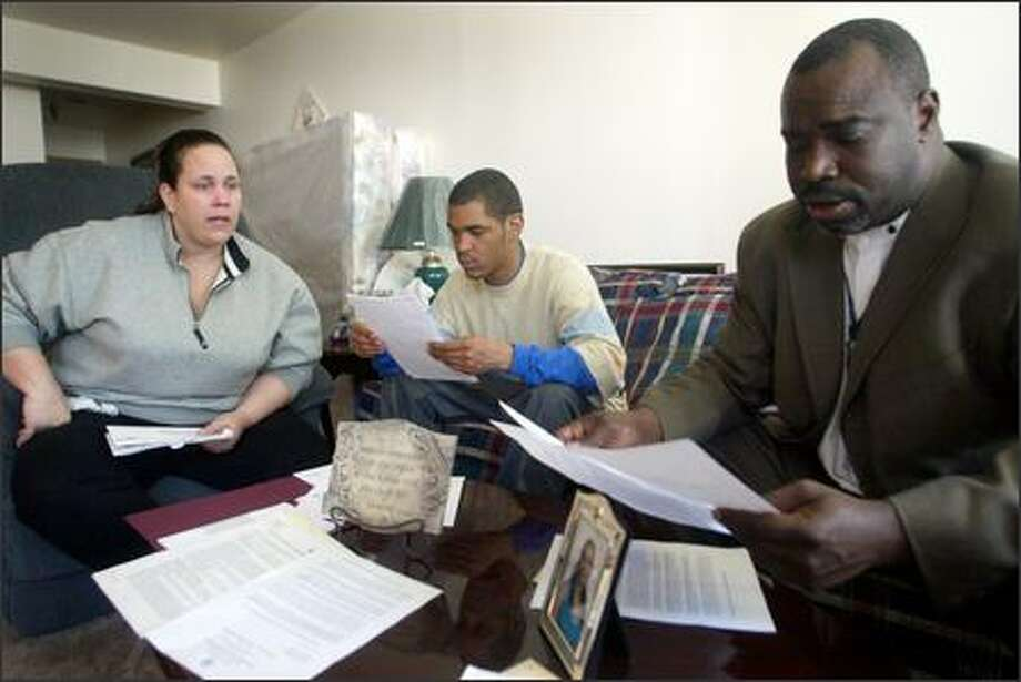 A former resident of New Orleans, Joan Berniard, and her oldest son, Larry Berniard, speak with John Manning from the Seattle Housing Authority over letters she's received trying to evict her and her family from their apartment in West Seattle. Photo: Karen Ducey/Seattle Post-Intelligencer