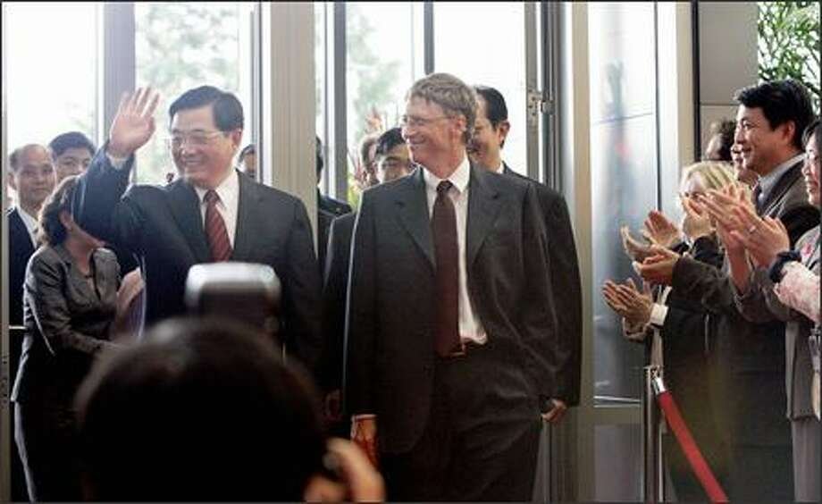 Chinese President Hu Jintao arrives at Microsoft headquarters with Chairman Bill Gates as Microsoft employees applaud in Redmond on Tuesday. Photo: AP