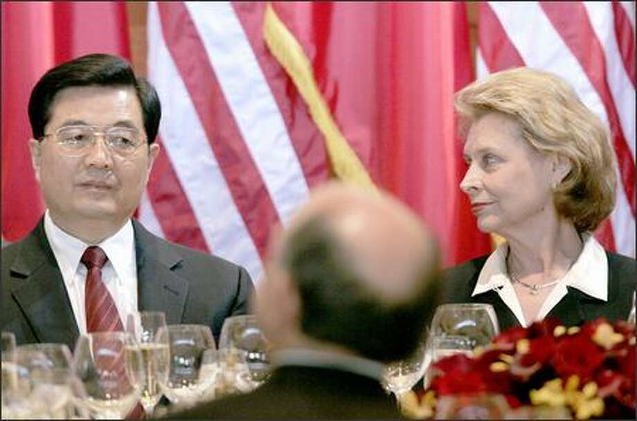 Chinese President Hu Jintao, left, sits with Washington Gov. Chris Gregoire at the head table Tuesday during dinner at Bill Gates' home. (AP Photo/Ted S. Warren, Pool) Photo: The Associated Press