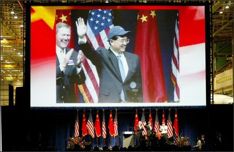 Wearing a Boeing cap, Chinese President Hu Jintao waves to workers Wednesday at the Everett plant. At left, Boeing exec Alan Mulally. Photo: PAUL JOSEPH BROWN/P-I
