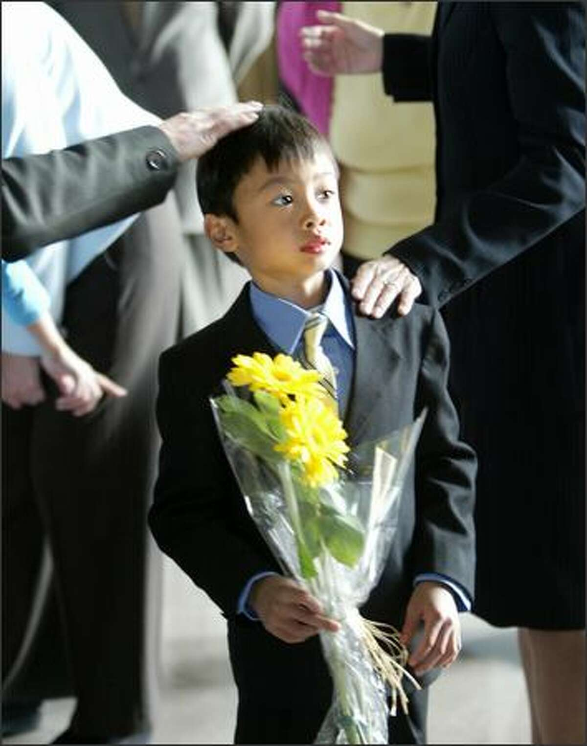 Seven-year-old Dylan Locke, son of former Gov. Gary Locke, waits to present flowers to China's Hu Jintao upon the president's arrival at a luncheon Wednesday at the Future of Flight Museum in Mukilteo with Washington dignitaries.