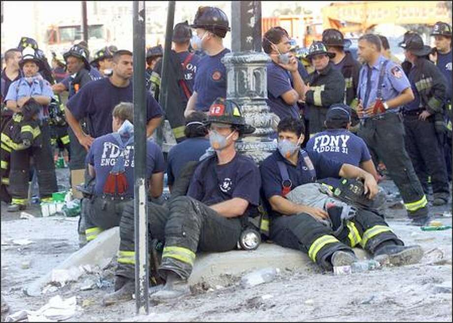 Firefighters rest during rescue efforts a day after the Sept. 11, 2001, attacks in New York. The disaster is still claiming lives. Photo: / Associated Press