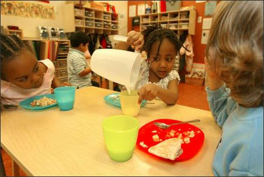 Joi Porter-Harris, 4, watches the last drop of milk dribble out of a pitcher as Nikyle Wilson, 4, at left, and Brandon Levinwood, 5, look on, at Seed of Life Center for Early Learning and Preschool. Studies have shown how critical early education is. Photo: Grant M. Haller/Seattle Post-Intelligencer