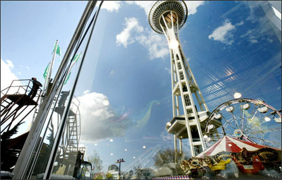 """Mike Santos, a Fun Forest maintenance worker, replaces flags Friday in the amusement park. A Seattle Center task force report criticizes the Fun Forest, saying """"it needs a fresh infusion of vision."""" Photo: Dan DeLong/Seattle Post-Intelligencer"""