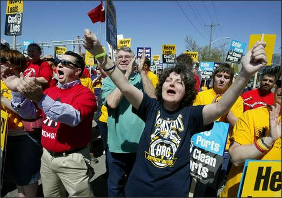 Teamster Debbie Dahlman, center, and Omar Perestrejo, left, of Unite Here Local 8 cheer with ralliers on Monday at Terminal 46. Photo: Scott Eklund/Seattle Post-Intelligencer