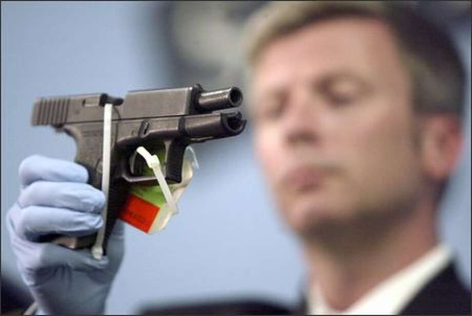 Seattle Detective James Danielson displays a Glock 9 mm, the type of gun used in Sunday's shooting in the 9700 block of Wallingford Avenue. A policeman was wounded before the gunman took his own life. Photo: Jim Bryant/Seattle Post-Intelligencer