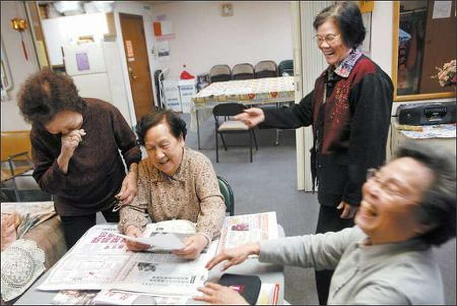 Jin Tao Xiong, center, laughs with friends Siu-Lan Yiu Yeung, left, Qui Feng Peng and Wai Ching, right, at the Sunshine Garden Chinese Senior Day Care Center, part of the Chinese Information and Service Center. Its staff hopes to move the 9,000-square-foot service center into a 17,000-square-foot space in August. Photo: Karen Ducey/Seattle Post-Intelligencer