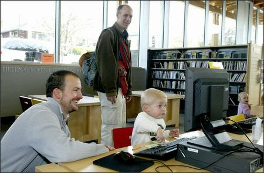 Michael Linscott, left, and his son, Emerson, check a computer at the Ballard Library last week. They were on a day trip to Ballard with Scott Steinhorst, center, and his daughter. Linscott and Steinhorst stay at home to care for their kids while their wives work. Photo: Gilbert W. Arias/Seattle Post-Intelligencer