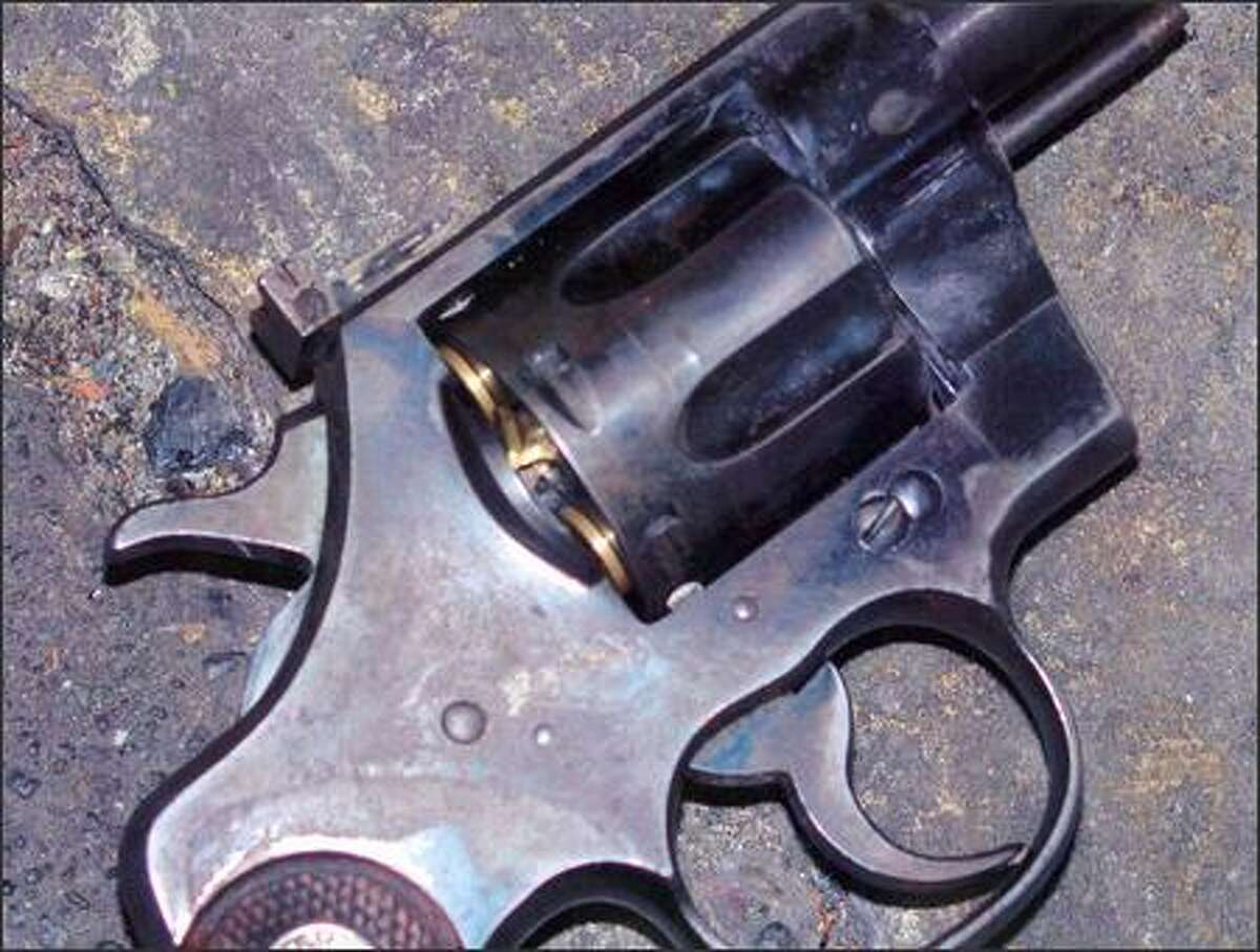 This photo, which was provided by the Seattle Police Department, shows the brass cartridge being pushed out the rear of the cylinder on the gunman's revolver.