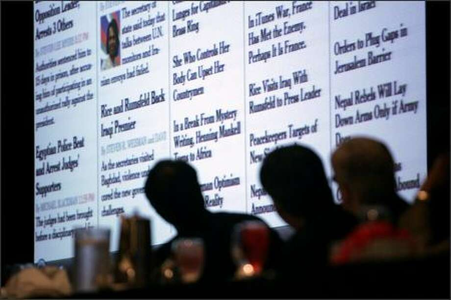 Participants at a newspaper editors convention Friday look at an enlarged version of a computer screen displaying an edition of The New York Times. Photo: / Associated Press