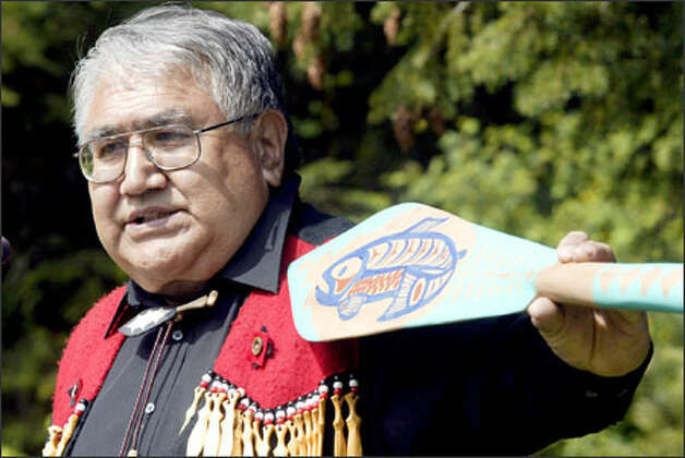 Suquamish tribe elder Gene Jones presents a canoe paddle he carved from a 2,500-year-old tree to Nancy Malmgren during memorial services for her husband, Les Malmgren, on Sunday. Photo: Jim Bryant/Seattle Post-Intelligencer / SEATTLE POST-INTELLIGENCERF