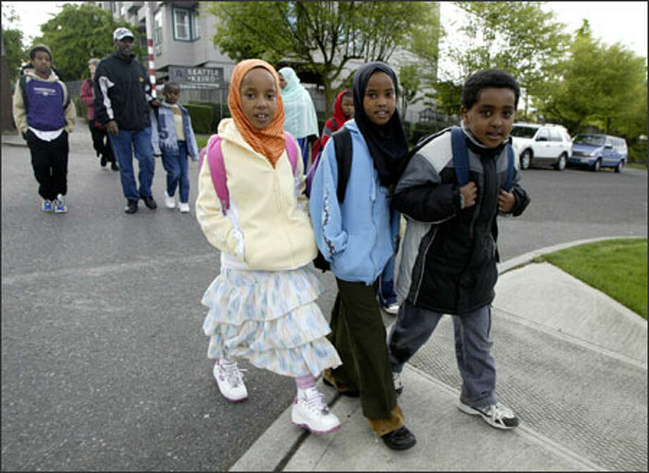 "From left, Gabbiftu Aliye, 7, Asanti Umar, 8, and Tumuuda Tamaami, 8, walk to Bailey Gatzert Elementary on Monday under the ""Walking School Bus"" program. Photo: Jim Bryant/Seattle Post-Intelligencer / Seattle Post-Intelligencer"