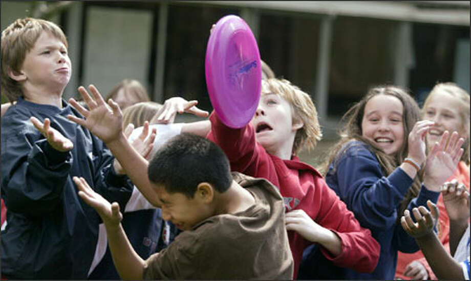 Casey deVarona, in red, catches a Frisbee at Catharine Blaine Elementary School as the lessons learned during SunWise Day turned into a Frisbee toss for the fourth-graders. Photo: Jim Bryant/Seattle Post-Intelligencer / Seattle Post-Intelligencer